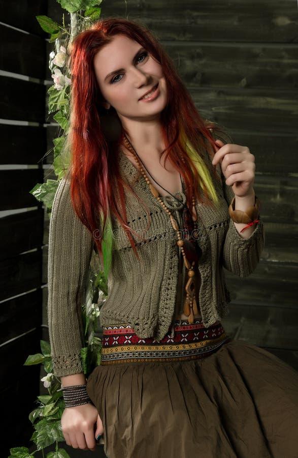 Mulher nova do ruivo do boho da hippie que tem o divertimento em um balanço Estilo da hippie em um fundo de madeira foto de stock