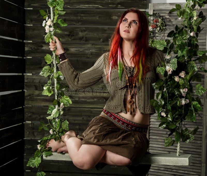 Mulher nova do ruivo do boho da hippie que tem o divertimento em um balanço Estilo da hippie em um fundo de madeira imagem de stock royalty free