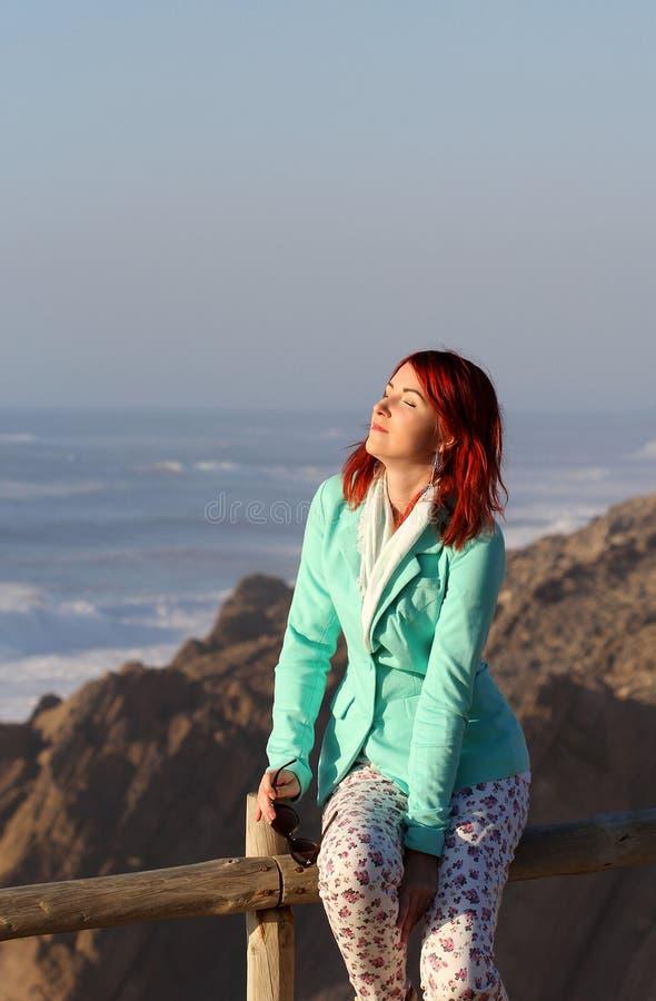 A mulher nova do ruivo que aprecia a luz solar no litoral imagens de stock