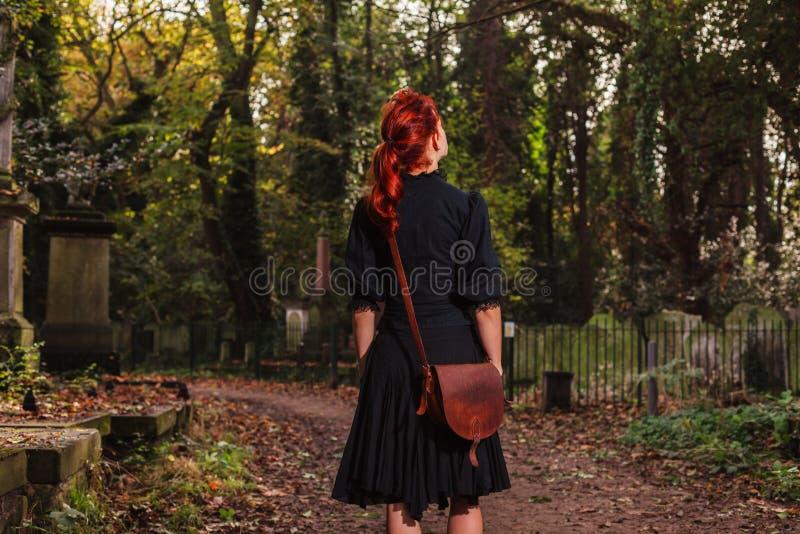 Mulher nova do ruivo que está no cemitério imagens de stock royalty free