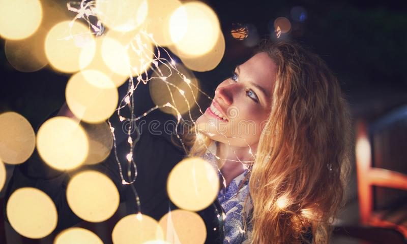 Mulher nova do ruivo surpreendida por luzes feericamente com bokeh fotografia de stock