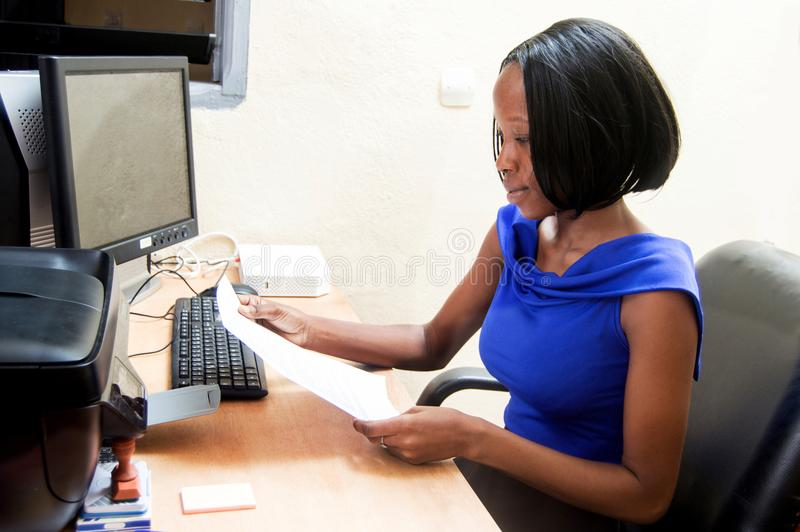 Mulher nova do secretário na frente de seu computador imagem de stock royalty free