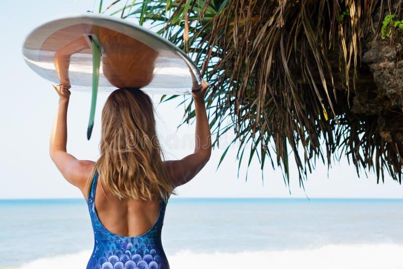 Mulher nova do surfista com caminhada da prancha na praia fotografia de stock