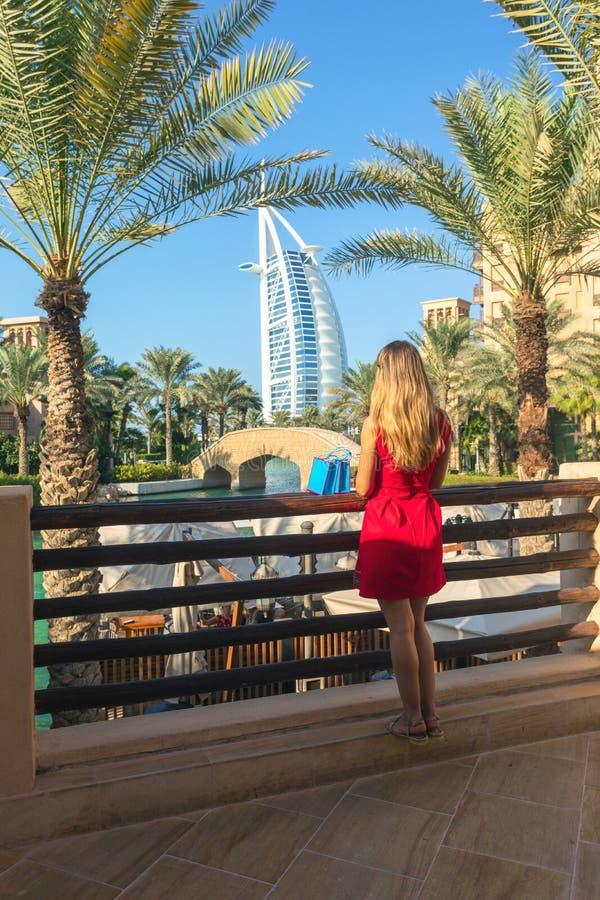 Mulher nova do turista vestida no vestido vermelho que olha o árabe do al de Burj do souk de Madinat Jumeirah com os sacos de com fotografia de stock