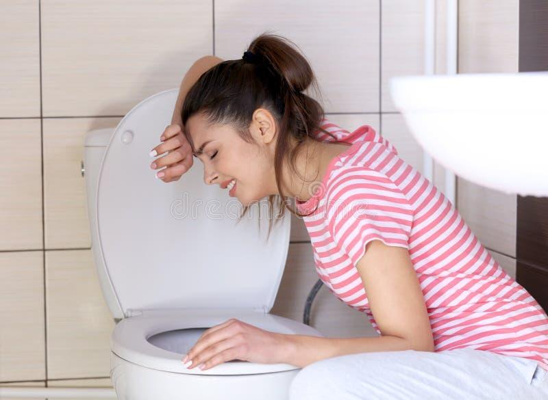 Mulher nova do vômito perto da bacia de toalete foto de stock royalty free