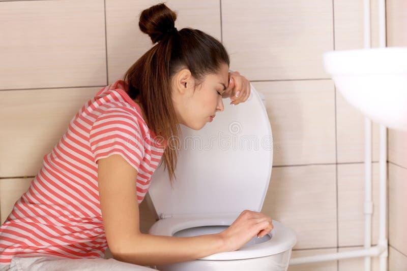 Mulher nova do vômito perto da bacia de toalete em foto de stock
