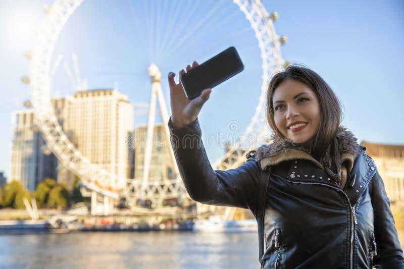 A mulher nova do viajante fala um selfie na frente das atrações sightseeing principais em Londres, Reino Unido foto de stock