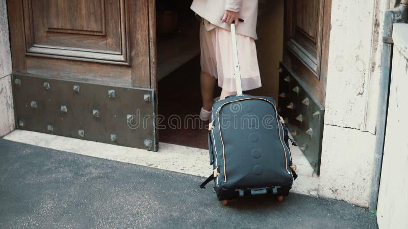 Mulher nova do viajante que anda com uma mala de viagem na rua A menina abre a porta e entra um arco fotos de stock royalty free