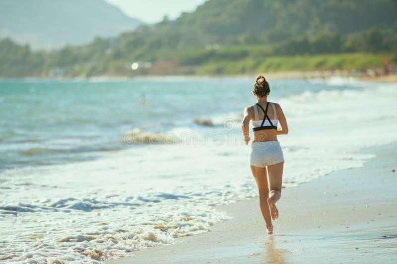 Mulher nova dos esportes na costa do oceano em movimentar-se da noite foto de stock royalty free