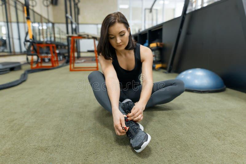 Mulher nova dos esportes que descansa no assoalho após exercícios no gym Aptidão, esporte, treinamento, pessoa, conceito saudável fotos de stock