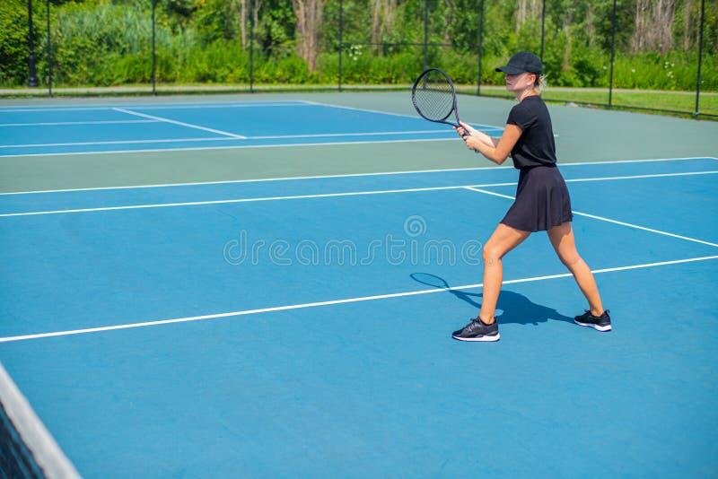 Mulher nova dos esportes que joga o tênis no campo de tênis azul imagem de stock