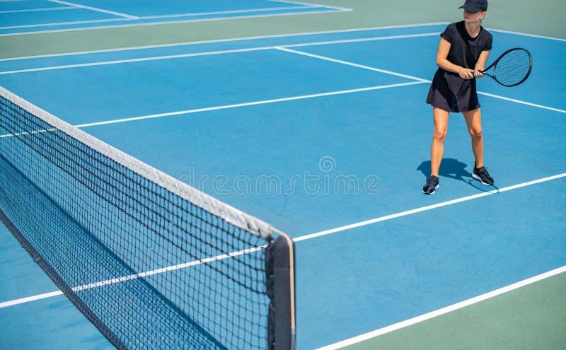 Mulher nova dos esportes que joga o tênis no campo de tênis azul imagem de stock royalty free