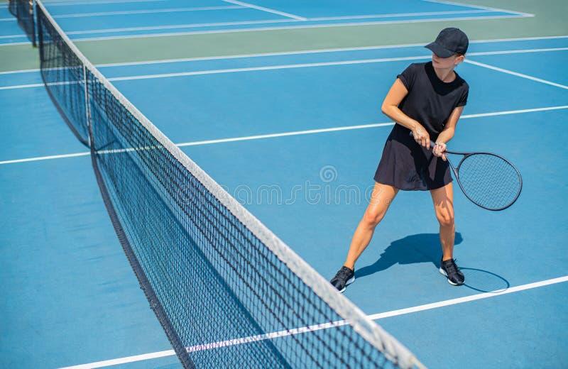 Mulher nova dos esportes que joga o tênis no campo de tênis azul fotografia de stock