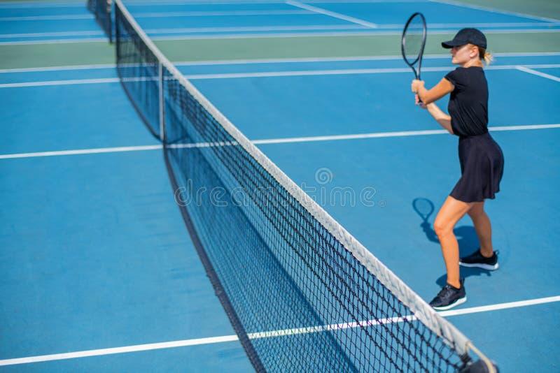 Mulher nova dos esportes que joga o tênis no campo de tênis azul foto de stock
