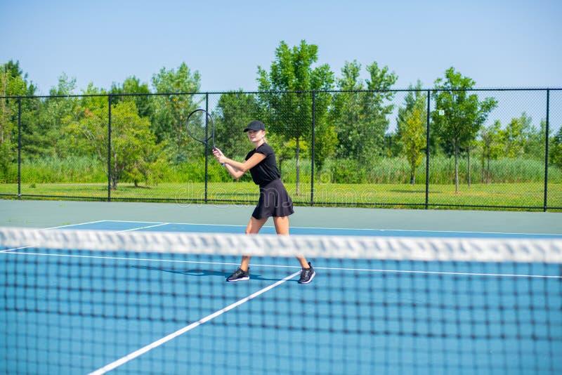 Mulher nova dos esportes que joga o tênis no campo de tênis azul fotos de stock