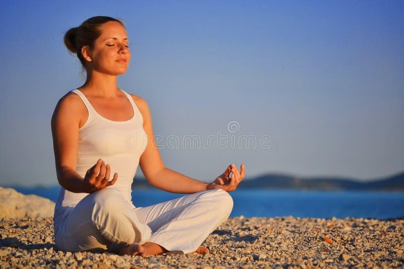 Mulher nova durante a meditação da ioga na praia foto de stock