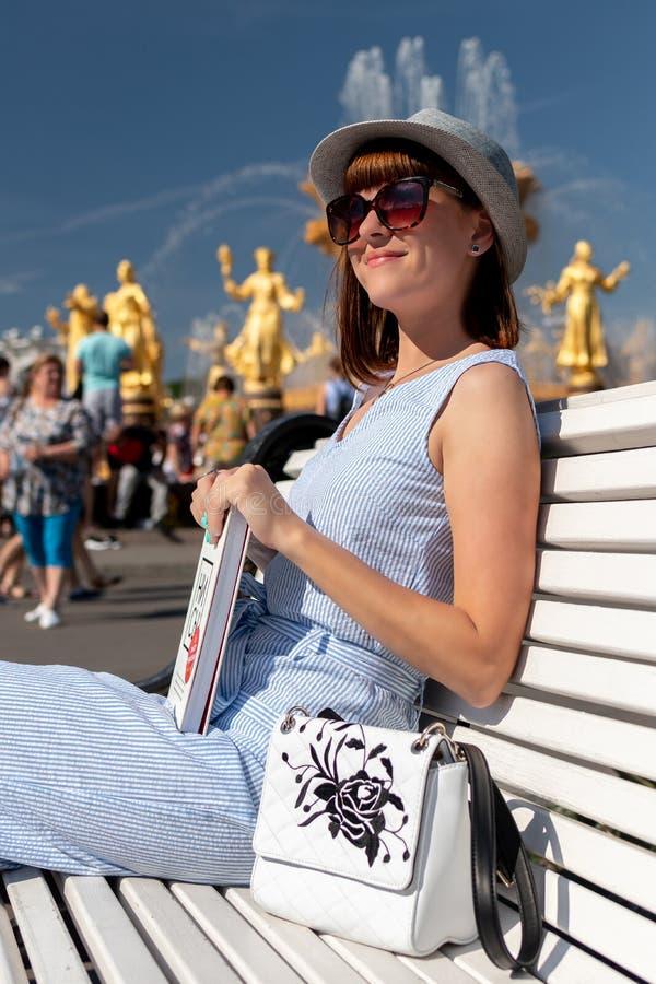 Mulher nova e à moda feliz com o chapéu e o livro que sentam-se no banco no parque imagens de stock royalty free