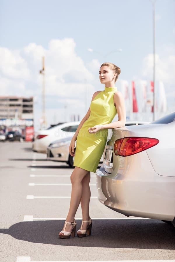 Mulher nova e à moda que está o carro próximo foto de stock royalty free