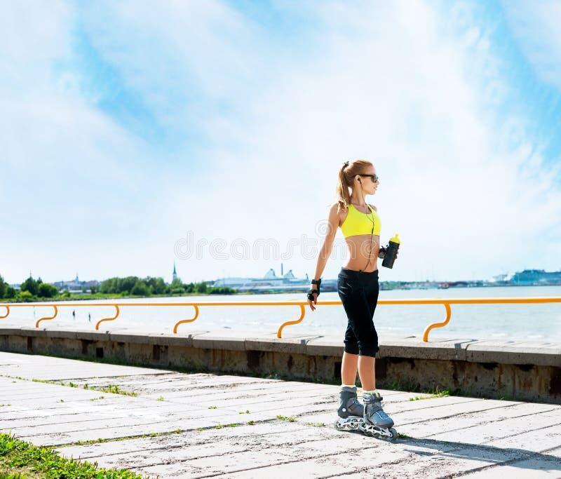 Mulher nova e apta que rollerblading em patins imagens de stock royalty free