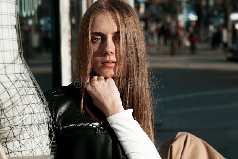 A mulher nova e bonita está sentando-se em um banco na rua e está levantando-se para a câmera fotografia de stock