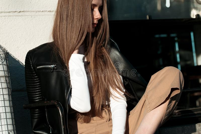 A mulher nova e bonita está sentando-se em um banco na rua e está levantando-se para a câmera foto de stock royalty free