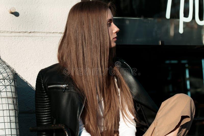 A mulher nova e bonita está sentando-se em um banco na rua e está levantando-se para a câmera imagens de stock