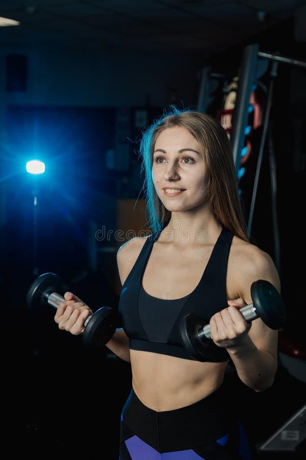 Mulher nova e bonita que dá certo com pesos no gym Ondas do bíceps imagens de stock royalty free