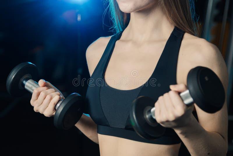 Mulher nova e bonita que dá certo com pesos no gym Ondas do bíceps fotografia de stock