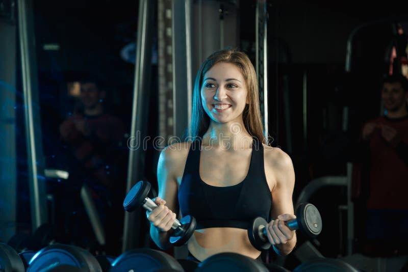 Mulher nova e bonita que dá certo com pesos no gym Ondas do bíceps foto de stock royalty free