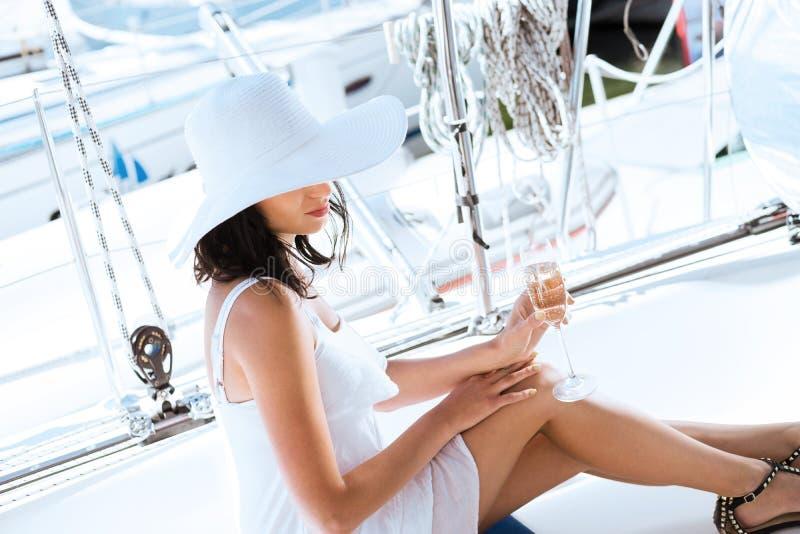 Mulher nova e bonita que relaxa em um barco de navigação luxuoso foto de stock royalty free