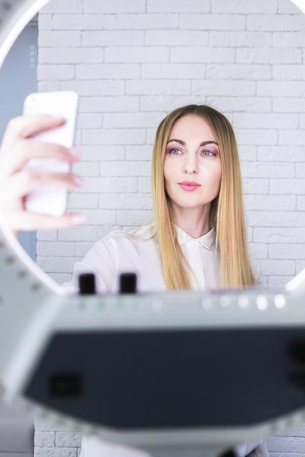 Mulher nova e bonita que toma o selfie com telefone celular no lig fotos de stock royalty free