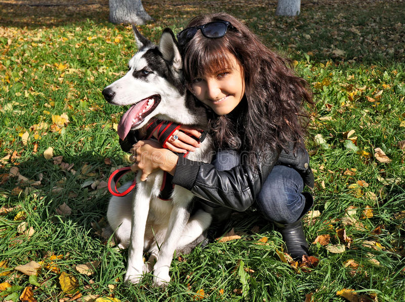 Mulher nova e cão de puxar trenós siberian do cão fotografia de stock royalty free