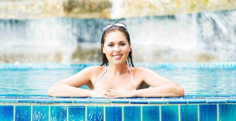 Mulher nova e desportiva no roupa de banho Menina que relaxa em uma associação no verão fotos de stock