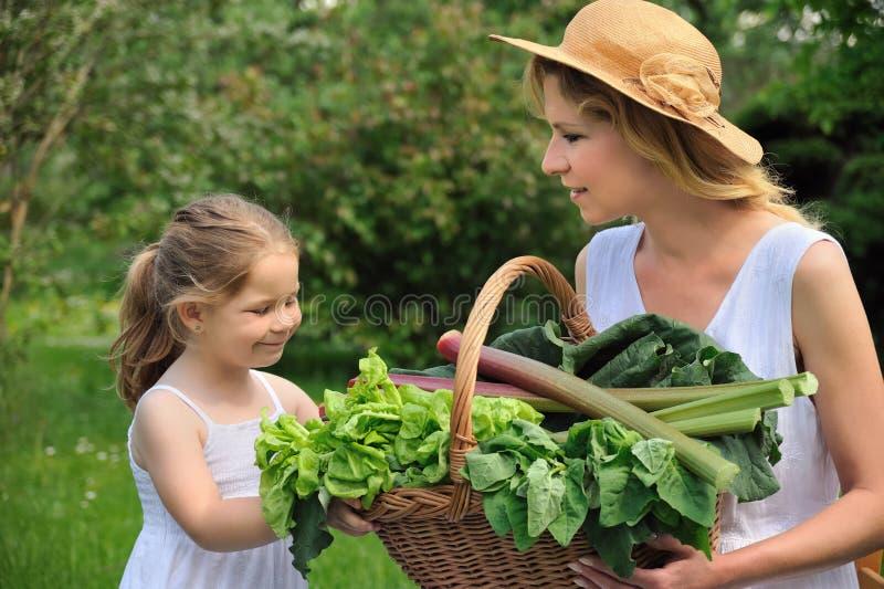 Mulher nova e filha com legume fresco fotos de stock royalty free