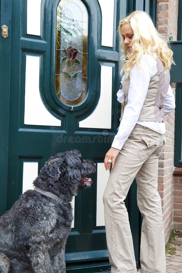 Mulher nova e seu cão na frente da casa. imagem de stock royalty free