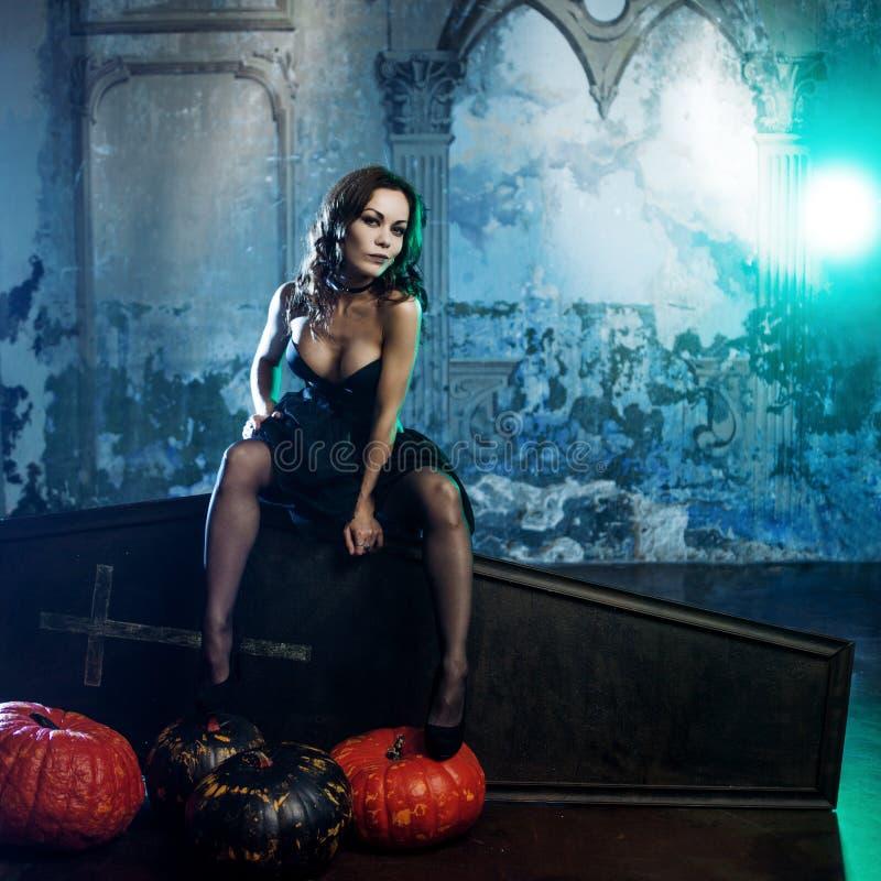 Mulher nova e 'sexy', imagem das bruxas em um cemitério que senta-se no caixão da tampa imagem de stock royalty free