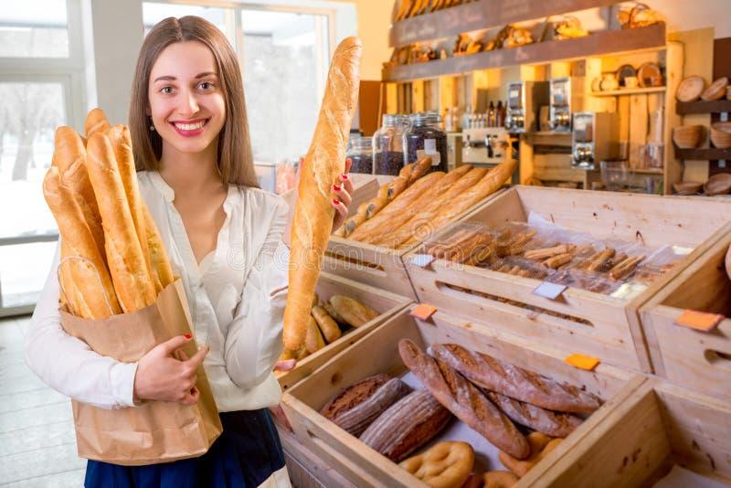 Mulher nova e sorrindo com os baguettes na loja da padaria imagem de stock