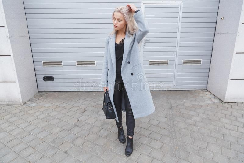 Mulher nova elegante do blodhair que veste o revestimento cinzento que levanta contra a parede áspera da rua foto de stock royalty free
