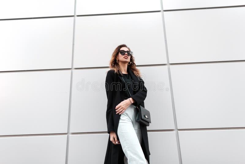 Mulher nova elegante do moderno na roupa à moda com uma bolsa de couro do vintage no levantamento preto na moda dos óculos de sol fotografia de stock royalty free