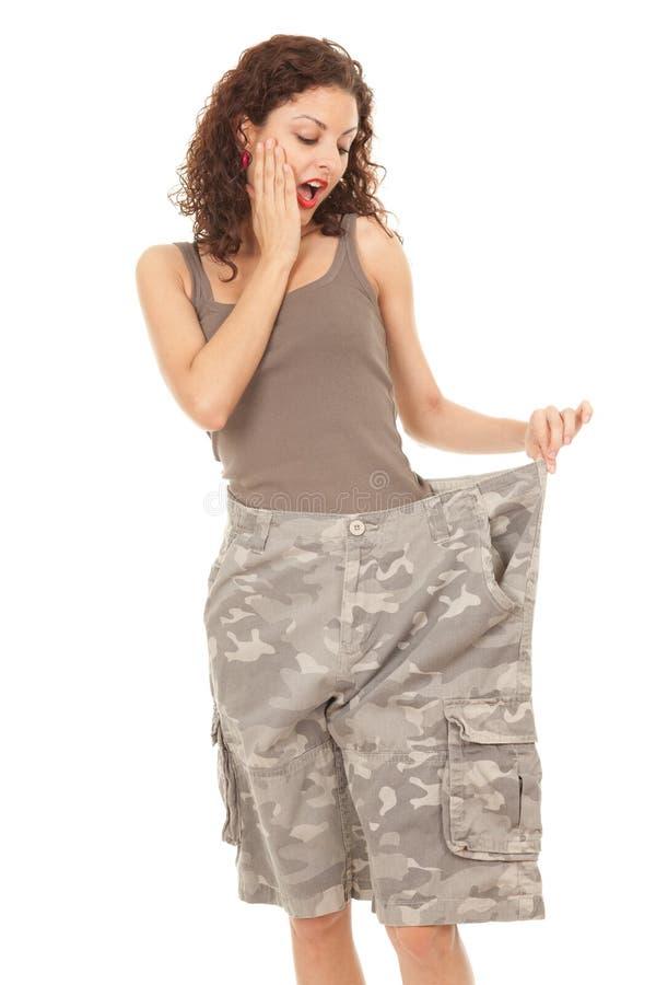 Mulher nova em calças demasiado grandes camuflar imagem de stock royalty free