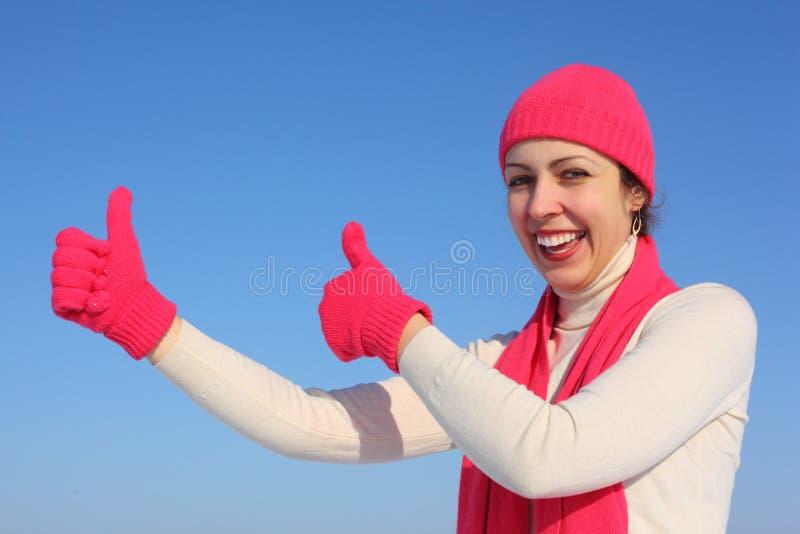 A mulher nova em luvas vermelhas mostra a aprovação do gesto fotografia de stock