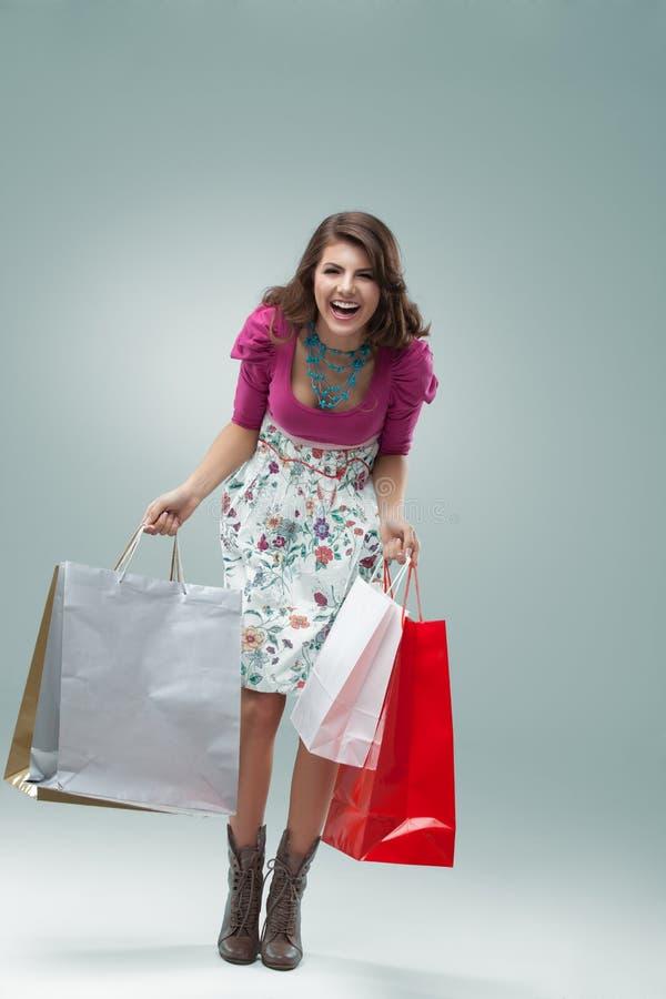 Mulher nova em sacos coloridos da terra arrendada do equipamento foto de stock
