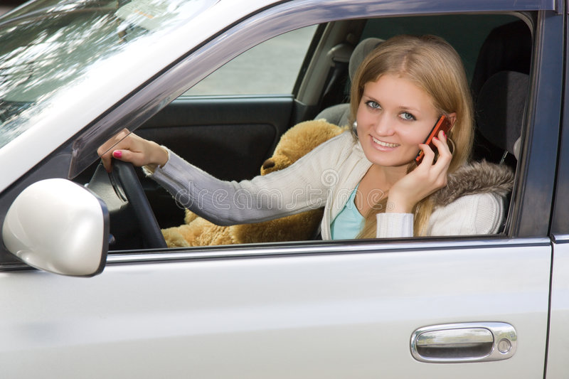 Mulher nova em seu carro quando no telefone de pilha fotografia de stock royalty free