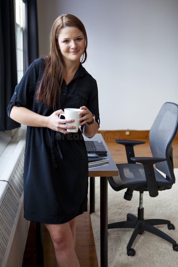 Mulher nova em seu escritório imagens de stock