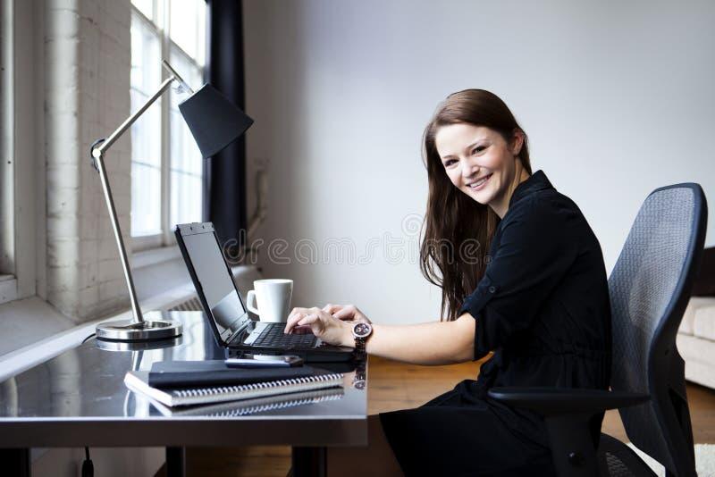Mulher nova em seu escritório foto de stock