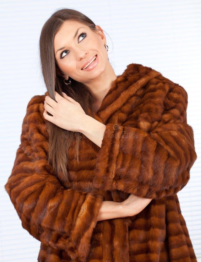 Mulher nova em um casaco de pele fotos de stock