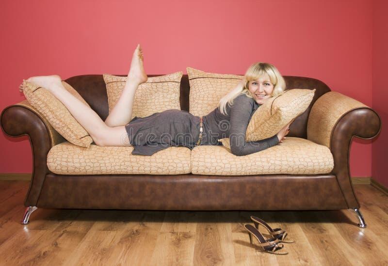 Mulher nova em um sofá foto de stock royalty free