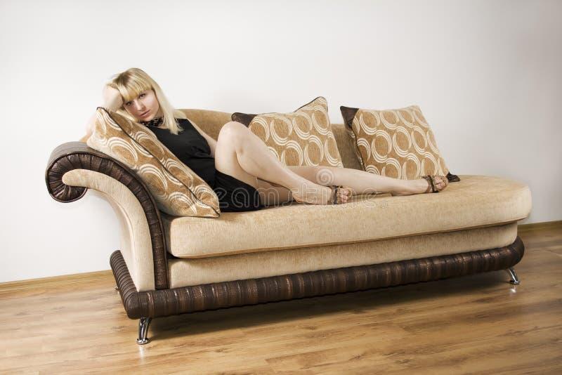 Mulher nova em um sofá fotografia de stock