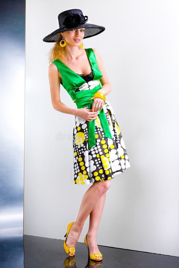 Mulher nova em um vestido e em um chapéu negro verdes imagens de stock
