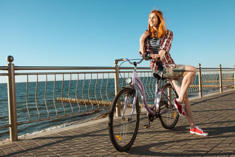 Mulher nova em uma bicicleta imagens de stock royalty free
